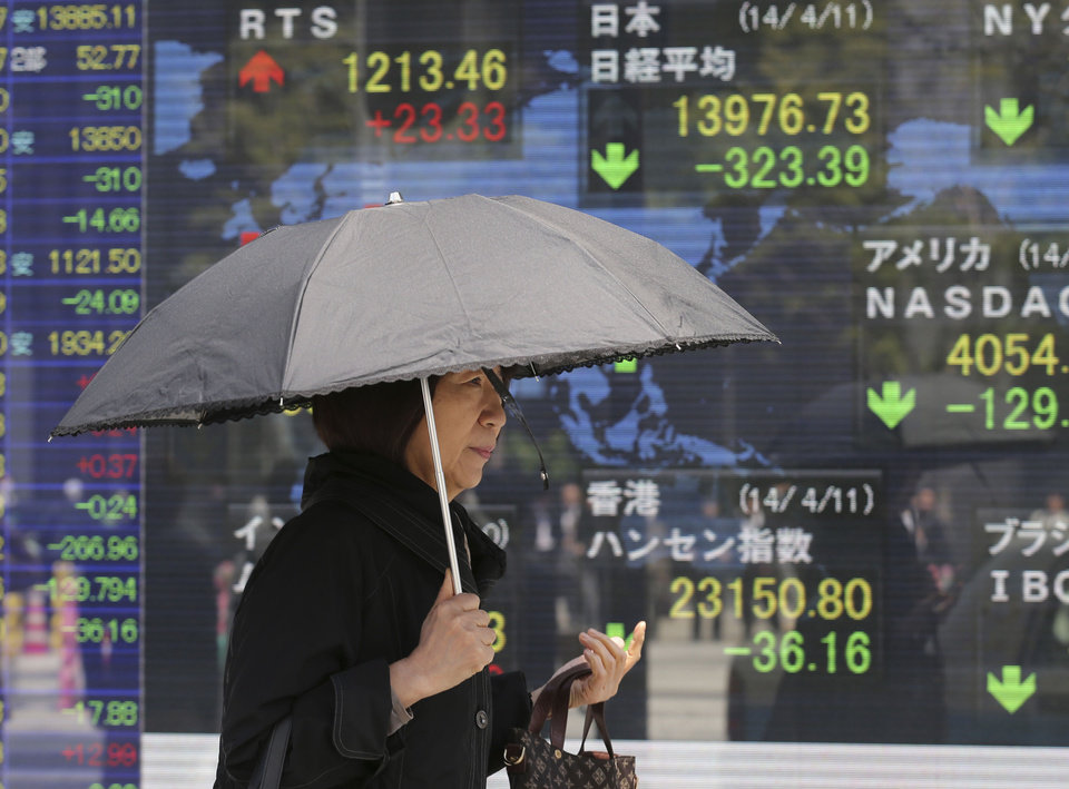 Photo - A woman walks by an electronic stock board of a securities firm in Tokyo, Friday, April 11, 2014. Tokyo's Nikkei 225 stock average fell more than 400 points at one point in morning trading. (AP Photo/Koji Sasahara)
