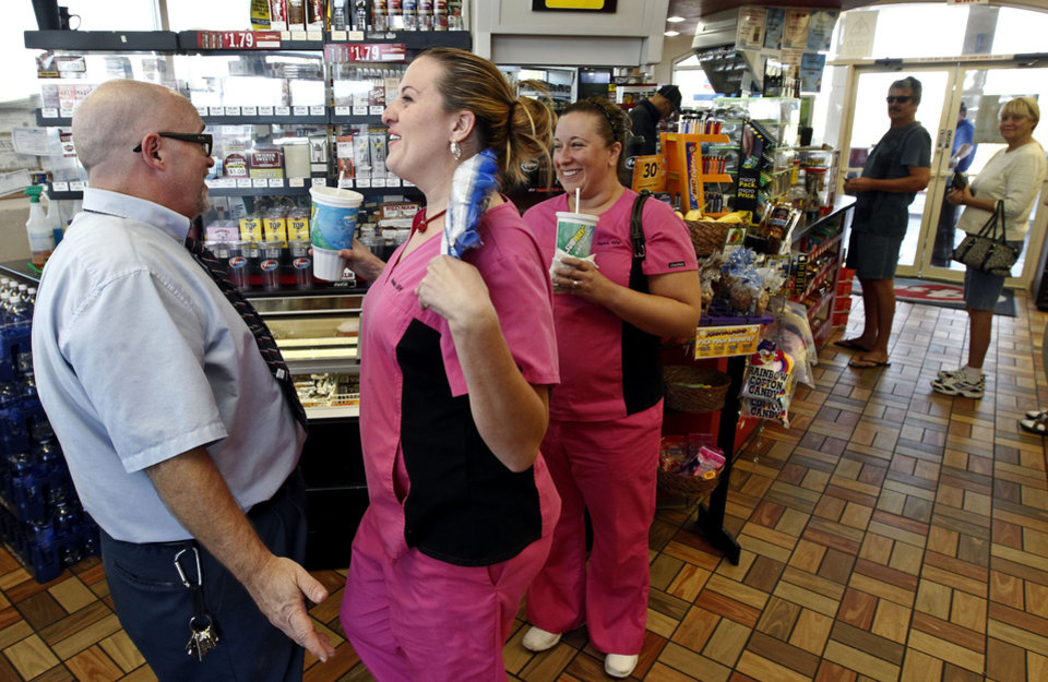 Store manager at 4 Sons Food Store, Bob Chebat, left, tells Brooke Elmore, middle, and Megan Hutto, that one of the winning tickets in the $579.9 million Powerball jackpot was purchased at the store, Nov. 29, 2012, in Fountain Hills, Ariz.(AP Photo/Ross D. Franklin)