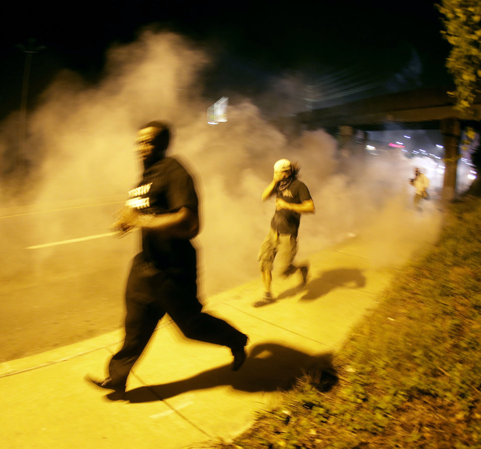 Photo - People run from tear gas after police dispersed a crowd Sunday, Aug. 17, 2014, during a protest for Michael Brown, who was killed by a police officer last Saturday in Ferguson, Mo. As night fell Sunday in Ferguson, another peaceful protest quickly deteriorated after marchers pushed toward one end of a street. Police attempted to push them back by firing tear gas and shouting over a bullhorn that the protest was no longer peaceful. (AP Photo/Charlie Riedel)