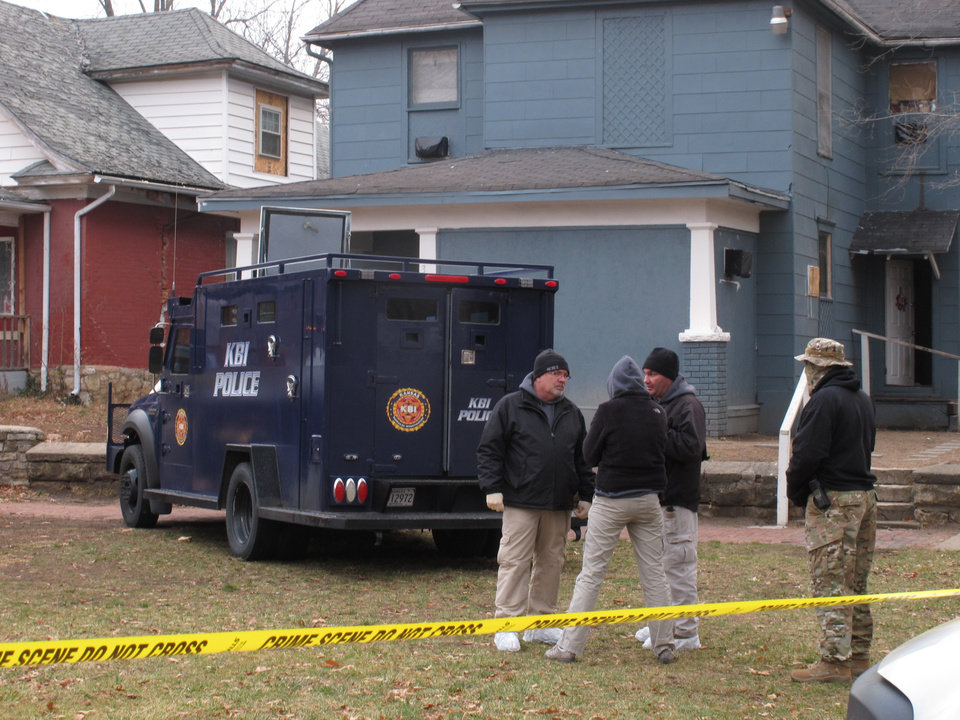 Photo - Kansas Bureau of Investigation agents confer outside a Topeka, Kan., home where a man suspected of fatally shooting two police officers was himself fatally shot by law enforcement officers, after a nearly two-hour armed standoff Monday, Dec. 17, 2012, in Topeka. The man was in the home; the KBI attempted to negotiate with him, but the talks failed. The Shawnee County sheriff's office, which is leading the investigation, said the man emerged from the home with a gun and officers opened fire.  (AP Photo/John Hanna)