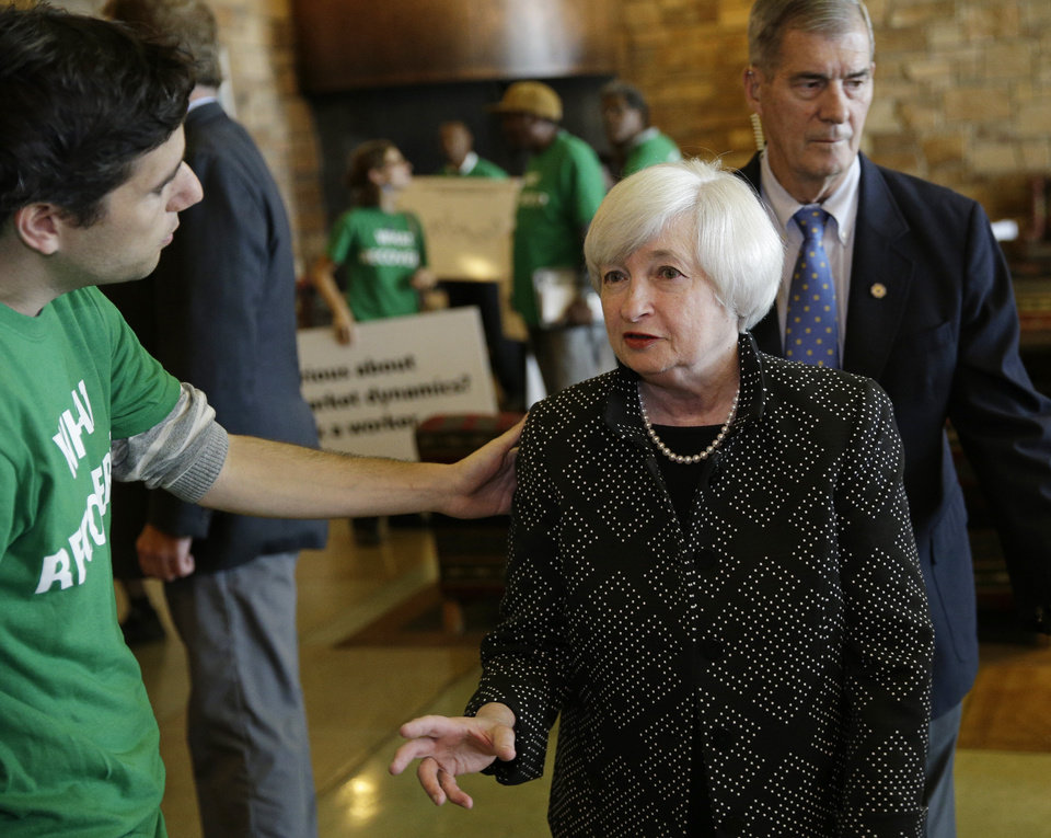 Photo - Federal Reserve Chair Janet Yellen, right, speaks with Ady Barkan of the Center for Popular Democracy as she arrives for a dinner during the Jackson Hole Economic Policy Symposium at the Jackson Lake Lodge in Grand Teton National Park near Jackson, Wyo. Thursday, Aug. 21, 2014. (AP Photo/John Locher)