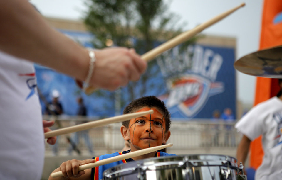 Photo - Bly Gomez, 3, of Edmond plays with the Thunder drummers before game 4 of the Western Conference Finals in the NBA basketball playoffs between the Dallas Mavericks and the Oklahoma City Thunder at the Oklahoma City Arena in downtown Oklahoma City, Monday, May 23, 2011. Photo by Bryan Terry, The Oklahoman