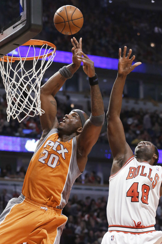 Photo - Phoenix Suns center Jermaine O'Neal, left, shoots past Chicago Bulls center Nazr Mohammed during the first half of an NBA basketball game in Chicago on Saturday, Jan. 12, 2013. (AP Photo/Nam Y. Huh)