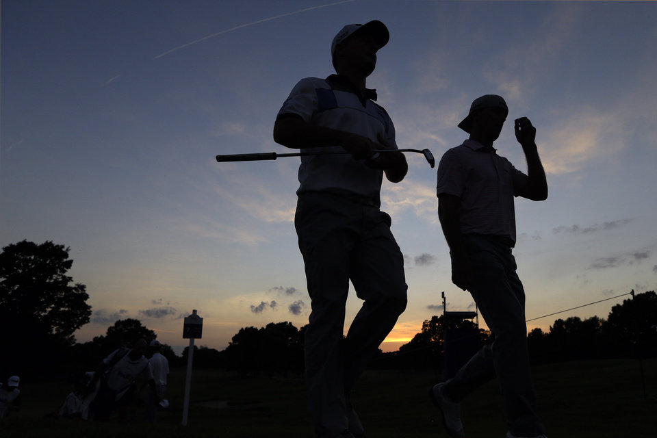 Photo - Golfers Matt Every, left, and Billy Horschel, right, walk off the 7th green and head for the clubhouse after play was suspended because of darkness during the first round of the St. Jude Classic golf tournament Thursday, June 5, 2014, in Memphis, Tenn. Play was suspended earlier in the day because of bad weather. (AP Photo/Mark Humphrey)
