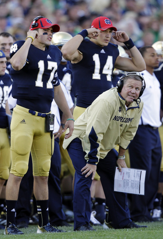 FILE - In this Sept. 8, 2012, file photo, Notre Dame head coach Brian Kelly watches as quarterback Charlie Fiessinger (17) and wide receiver Luke Massa (14) signal in a play during an NCAA college football game against Purdue in South Bend, Ind. For leading the Fighting Irish to the BCS championship game for the first time, Kelly was voted Associated Press college football coach of the year, Wednesday, Dec. 19, 2012.  (AP Photo/Michael Conroy, File)