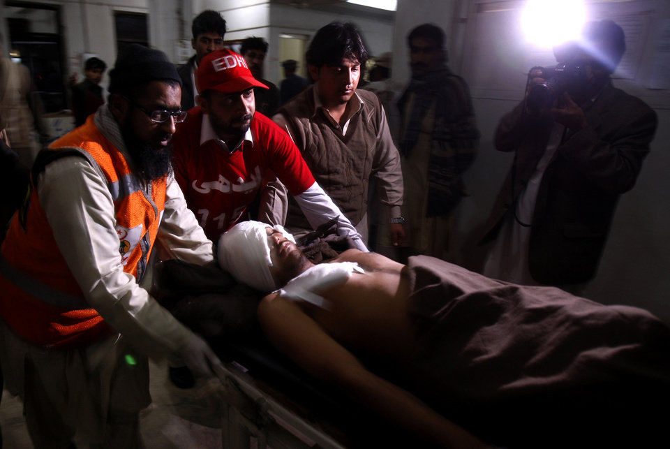 Photo - A Pakistani man who was injured in a suicide bombing is rushed by volunteers to a hospital in Peshawar, Pakistan, Friday, Feb. 1, 2013. A suicide bomber detonated his explosives outside a Shiite mosque in northwestern Pakistan as worshippers were leaving Friday prayers, killing several people and wounding dozens in the latest apparent sectarian attack in the country, police said.(AP Photo/Mohammad Sajjad)
