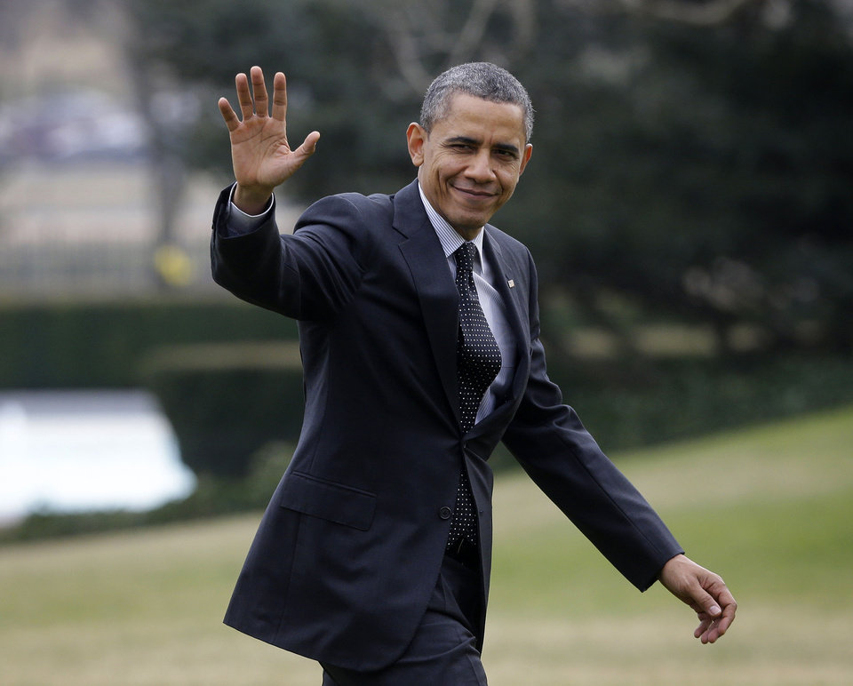 President Barack Obama waves as he walks across the South Lawn of the White House in Washington, Thursday, Feb. 7, 2013, following his arrival on Marine One helicopter from the House Democratic Issues Conference in Lansdowne, Va. (AP Photo/Pablo Martinez Monsivais)
