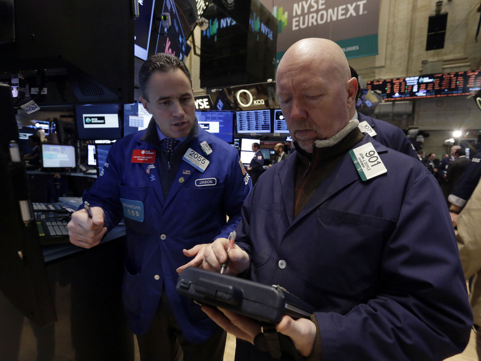 Photo - Specialist Jason Hardzewicz, left, and trader John Doyle work on the floor of the New York Stock Exchange Wednesday, Jan. 8, 2014.Stocks are mostly lower in early trading as investors hold back ahead of the release of the latest news from the Federal Reserve. (AP Photo/Richard Drew)