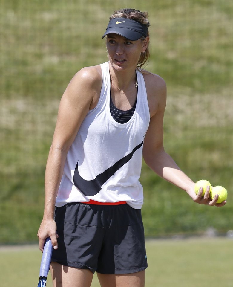 Photo - Maria Sharapova of Russia attends a practice session ahead of the All England Lawn Tennis Championships in Wimbledon, London,  Sunday June  22, 2014. The Championships start Monday June 23. (AP Photo/Sang Tan)
