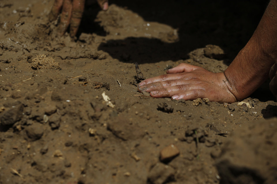 Photo - Palestinians use their hands to move soil soaked with water and shape the grave of a member of the al-Batsh family who were killed in Saturday's Israeli airstrike, during a funeral procession in Gaza City on Sunday, July 13, 2014. The strike hit the home of Gaza police chief Taysir al-Batsh and damaged a nearby mosque as evening prayers ended Saturday, killing at least 18 people, wounding 50 and leaving some people believed to be trapped under the rubble, said Palestinian Health Ministry official Ashraf al-Kidra. (AP Photo/Lefteris Pitarakis)