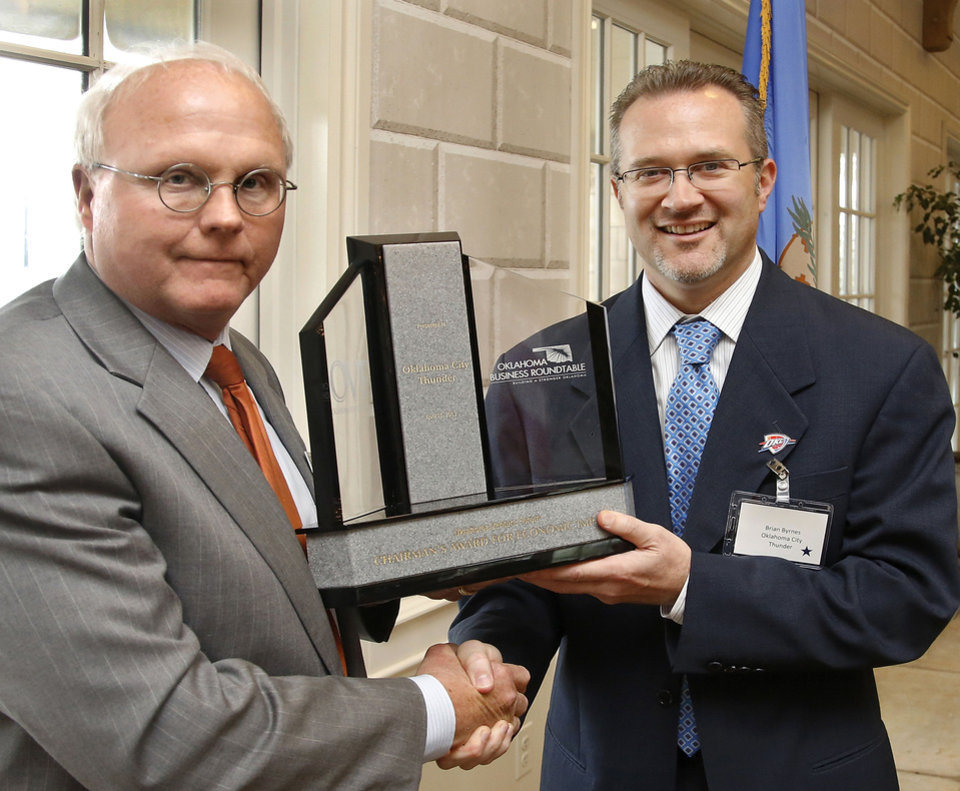 Bryan Byrnes, right, with the Oklahoma City Thunder, accepts an award from Gary Rosenhamer, director of the Oklahoma Venture Forum, on Wednesday at a luncheon inside the Phillips Pavilion on the grounds of the Governor�s Mansion.  Photo by Jim Beckel, The Oklahoman