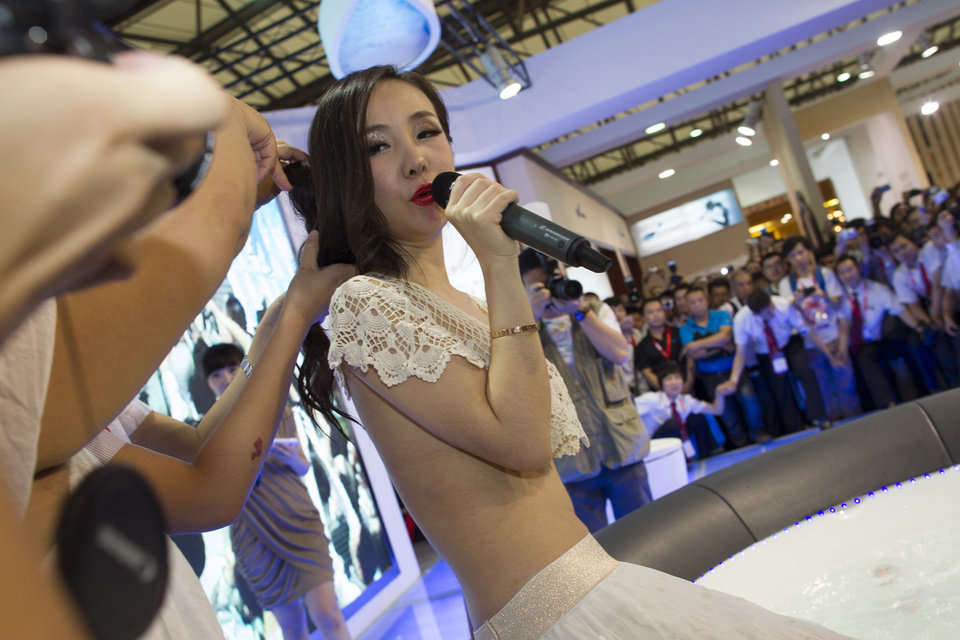 In this May 24, 2012 photo, Gan Lulu performs at a kitchen and toilet equipments expo in Shanghai, China. Regulators suspended a Chinese broadcaster Friday, Nov. 30, 2012, after an unaired segment of a TV game show was leaked online showing a raucous shouting match about nudity between spectators and a woman who calls her daughter the next Lady Gaga. The six-minute clip, still available on YouTube, shows Gan as well audience members and the model's mother shouting and swearing after one spectator asks whether Gan's risque images have undermined China's morality. (AP Photo)  CHINA OUT
