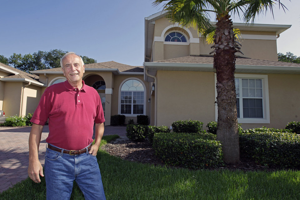 Photo -   In this Tuesday, July 31, 2012 photo, school teacher Larry Szrom stands in front of his home in Ocoee, Fla. Szrom makes a fraction of what he used to earn, but the former chemical engineer, mortgage broker and real estate developer is thrilled to be working as a high school chemistry teacher, a job he loves. Szrom, a registered Republican who supported John McCain in 2008, is now leaning toward President Barack Obama. He dismisses former Gov. Mitt Romney's claims that his business skills will get the economy moving. (AP Photo/John Raoux)