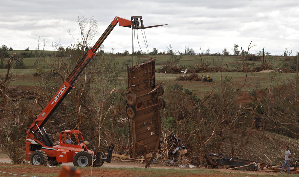 Photo - A lift truck removes what is left of a trailer west of El Reno, Wednesday, May 25, 2011. Photo by Chris Landsberger, The Oklahoman