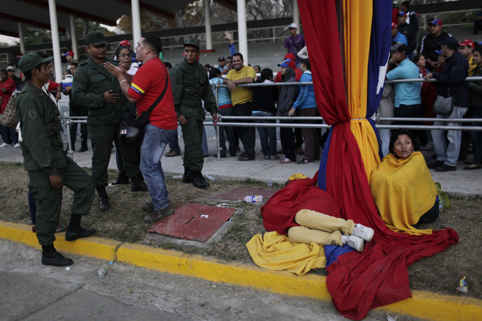 Photo - Security officers block a man trying to cut the line of people waiting to see the body of Venezuela's late President Hugo Chavez outside the military academy where he is lying in state in Caracas, Venezuela on Saturday, March 9, 2013. Chavez died on March 5, 2013 after a nearly two-year bout with cancer. He was 58. (AP Photo/Rodrigo Abd)