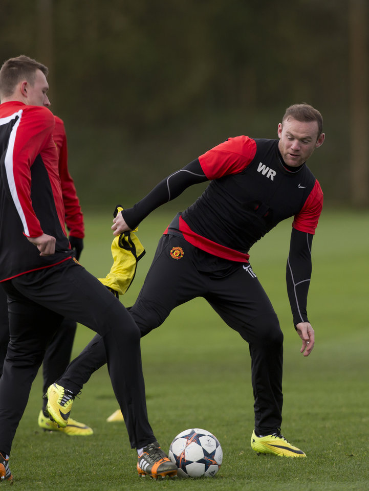 Photo - Manchester United's Wayne Rooney, right, trains with teammates at Carrington training ground in Manchester, Tuesday, April 8, 2014. Manchester United will play Bayern Munich in Germany in a Champions League quarter final second leg soccer match on Wednesday. (AP Photo/Jon Super)