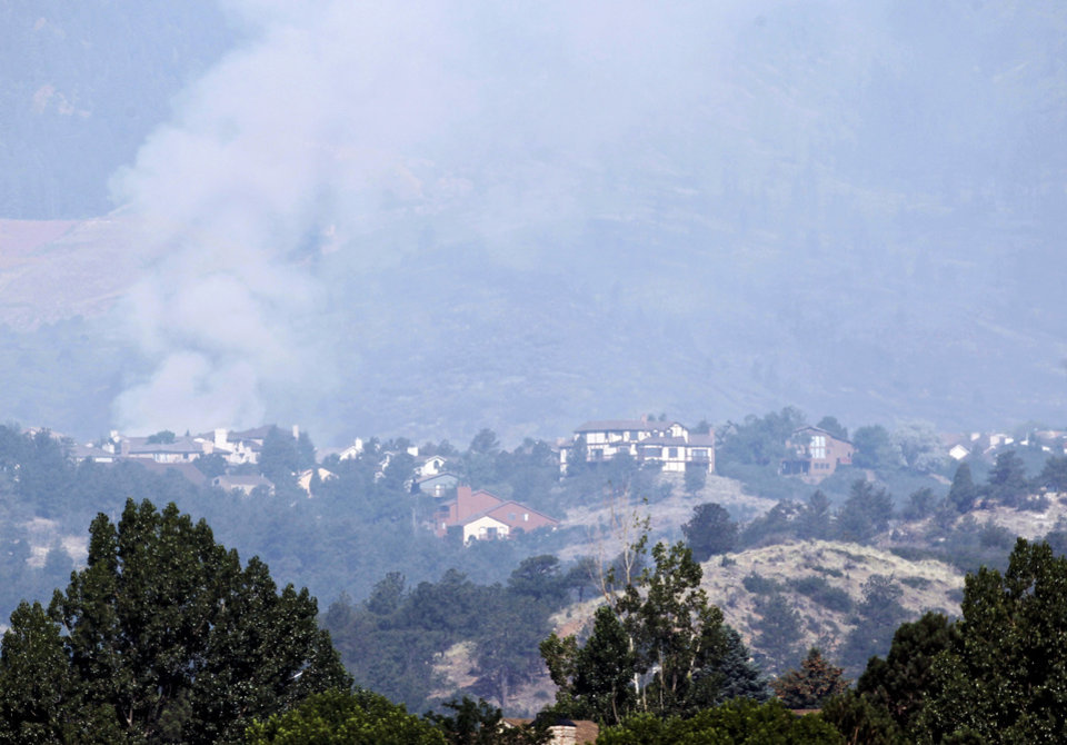 Photo -   A plume of smoke from the Waldo Canyon wildfire rises behind homes west of Colorado Springs, Colo., Wednesday, June 27, 2012. A large number of homes were destroyed by the fire Tuesday night in subdivisions west of Colorado Springs. (AP Photo/Ed Andrieski)