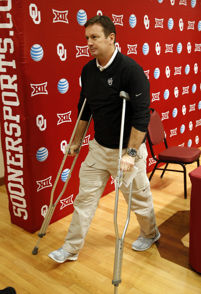 Photo - University of Oklahoma Sooners (OU) head football coach Bob Stoops leaves on crutches after he holds a press conference on Wednesday, Feb. 4, 2015  in Norman, Okla. Photo by Steve Sisney, The Oklahoman