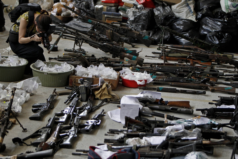 Photo - FILE - In this Nov. 30, 2010 file photo, a photojournalist takes pictures of weapons, drugs and ammunition seized by police in Rio de Janeiro, Brazil. Firearm-related deaths in Brazil are still among the highest in the world, even though the number of murders in the country has stabilized in recent years. (AP Photo/Felipe Dana, File)