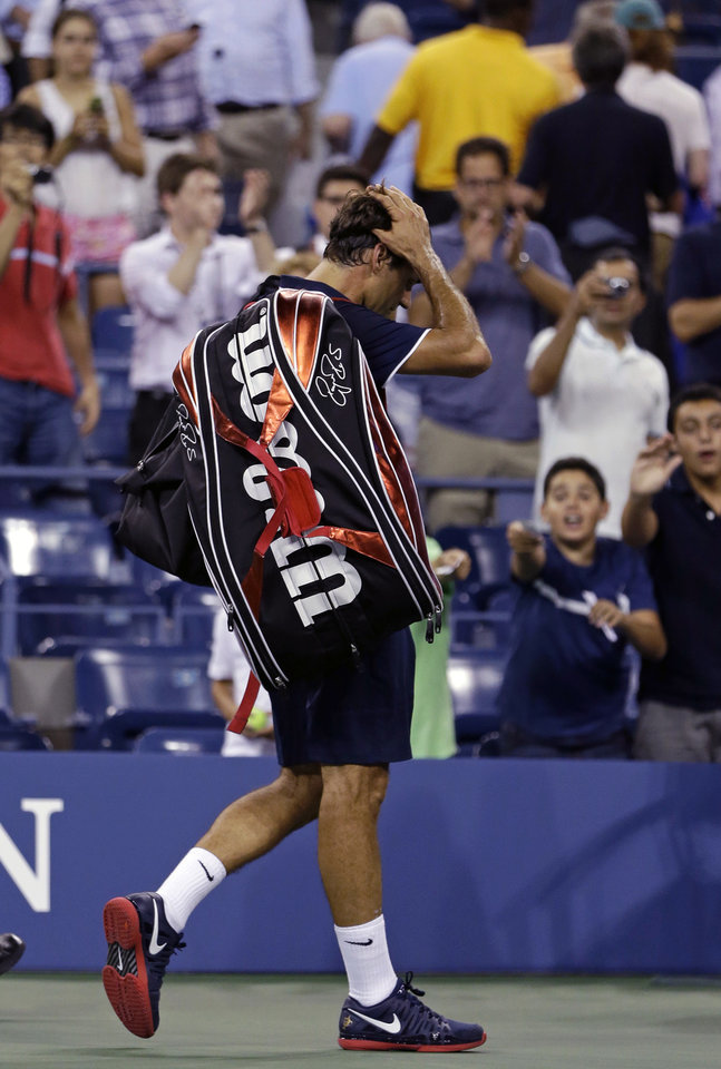 Photo -   Roger Federer, of Switzerland, leaves the court after being defeated by Tomas Berdych, of the Czech Republic, in a quarterfinals match at the U.S. Open tennis tournament on Wednesday, Sept. 5, 2012, in New York. Berdych won 7-6 (1), 6-4, 3-6, 6-3. (AP Photo/Darron Cummings)
