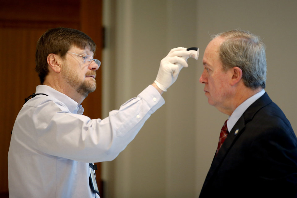 Photo - Phillip Parker with the Oklahoma State Department of Health checks the temperature of Sen. Mart Quinn as he enters the state Capitol in Oklahoma City, Monday, April 6, 2020. [Bryan Terry/The Oklahoman]