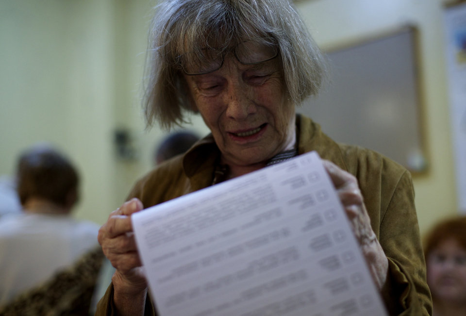 Photo - An Ukrainian woman reads her ballot at a polling station in Mariupol, Ukraine, on Sunday, May 25, 2014. Ukraine's critical presidential election got underway Sunday under the wary scrutiny of a world eager for stability in a country rocked by a deadly uprising in the east. (AP Photo/Ivan Sekretarev)
