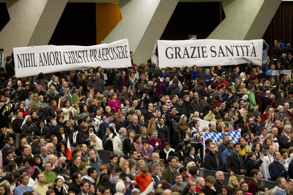 "Faithful hold banners reading in Latin ""Nihil amori Christi praeponere"" (Prefer nothing to the love of Christ), left, and in Italian ""Grazie Santita' "" (Thank you Your Holiness) during Pope Benedict XVI's weekly general audience in the Paul VI Hall at the Vatican, Wednesday Feb. 13, 2013. Looking tired but serene, Pope Benedict XVI told thousands of faithful Wednesday that he was stepping down for ""the good of the church,"" speaking in his first public appearance since dropping the bombshell announcement of his resignation. The 85-year-old Benedict basked in more than a minute-long standing ovation when he entered the packed audience hall for his traditional Wednesday general audience. (AP Photo/Alessandra Tarantino)"