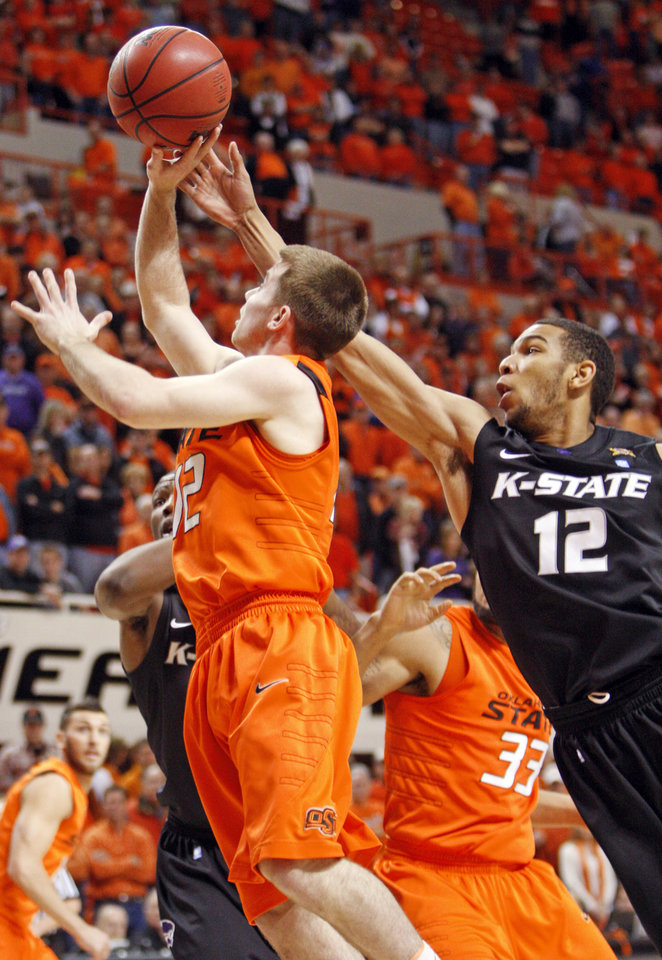 Photo - OSU's Keiton Page (12), left, takes a shot in front of Nick Russell (12) of KSU during the men's college basketball game between Oklahoma State University (OSU) and Kansas State University (KSU) at Gallagher-Iba Arena in Stillwater, Okla., Saturday, January 8, 2011. Photo by Nate Billings, The Oklahoman