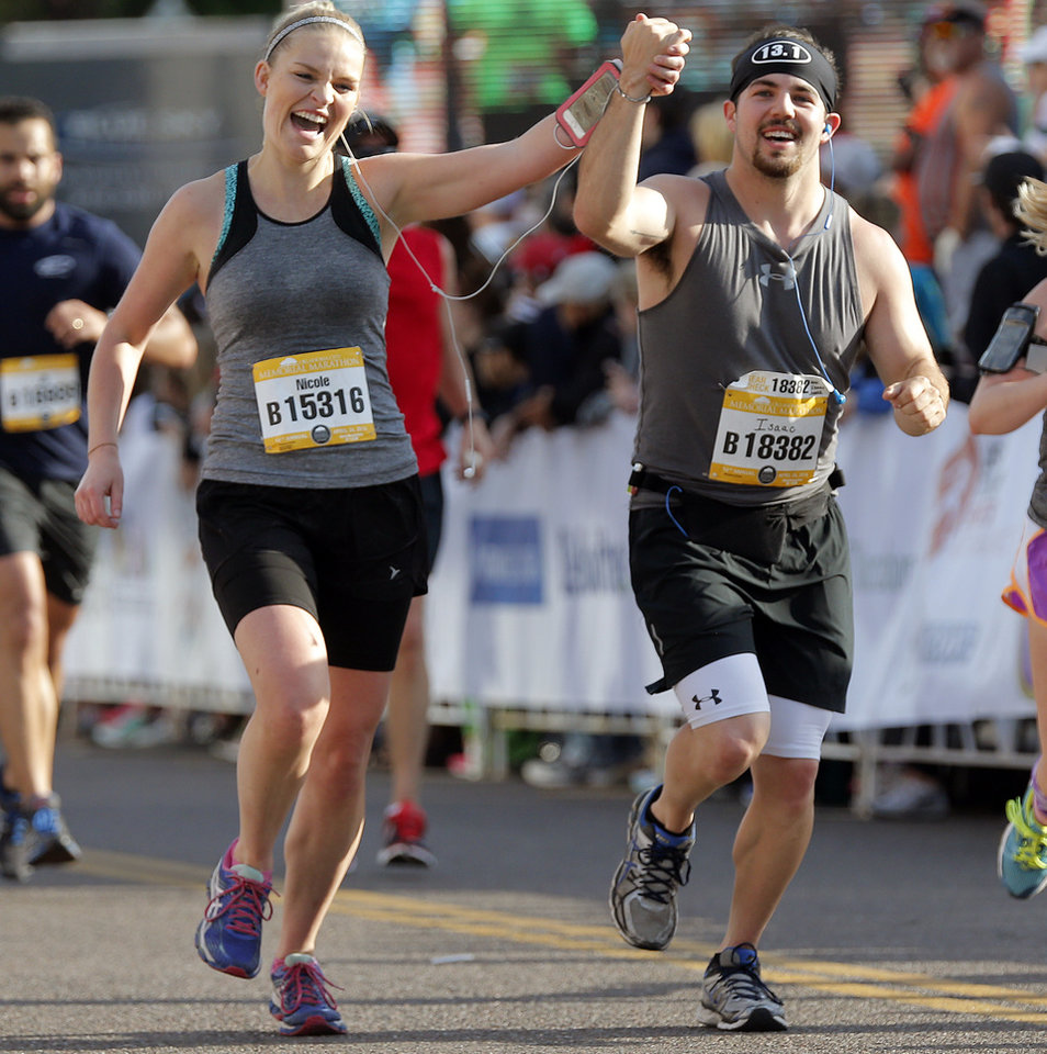 Photo - Nicole Taylor and Isaac Lewis cross the half marathon finish line hand-in-hand during the Oklahoma Memorial Marathon in Oklahoma City, Okla. on Sunday, April 24, 2016.   Photo by Chris Landsberger, The Oklahoman
