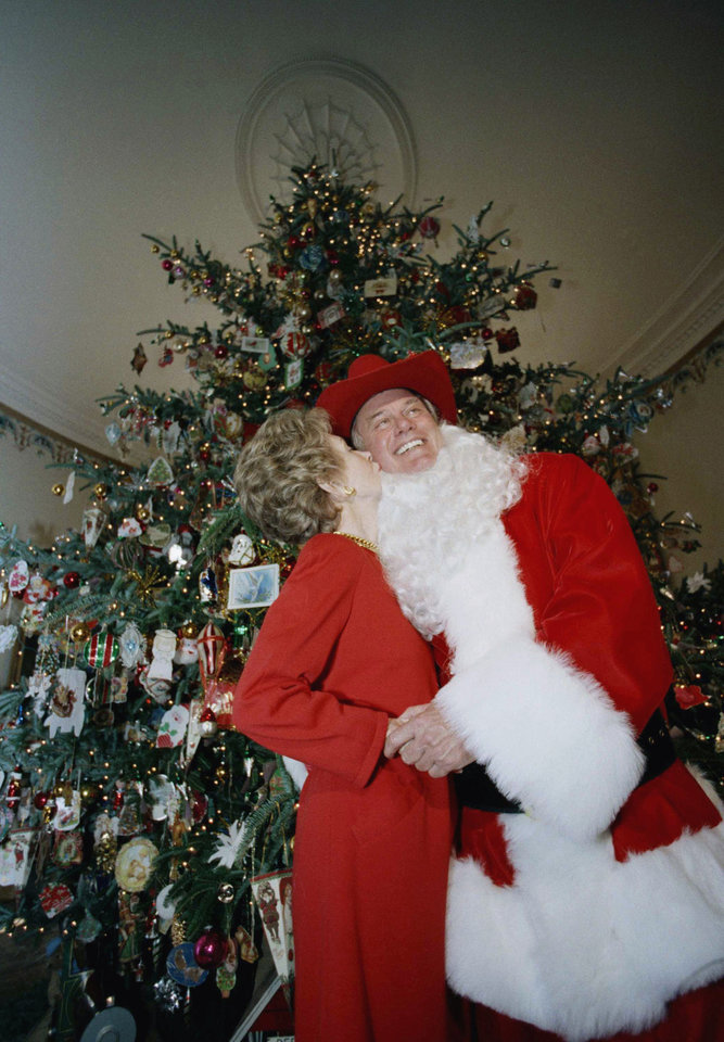 Photo -   FILE - In this Monday, Dec. 9, 1985 file photo, first lady Nancy Reagan kisses actor Larry Hagman, playing Santa Claus, at a showing of the holiday decorations at the White House in Washington. Actor Larry Hagman, who for more than a decade played villainous patriarch JR Ewing in the TV soap Dallas, has died at the age of 81, his family said Saturday Nov. 24, 2012. (AP Photo/Bob Daugherty, File)