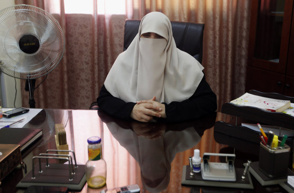 Photo - In this Monday, June 24, 2013 photo, Kifah Rantisi, 47, poses during an interview at her office in Gaza City. On the day of his induction, Baraa Rantisi, her son, was told to wait near a mosque. A white car drove up. Secret passwords were exchanged. And then he was sworn into the Muslim Brotherhood, an exclusive movement that sees itself on a divine mission to establish Islamic rule. AP reporters got rare access to the Rantisi family, the closest thing to a royal clan in the Brotherhood in Gaza, at a time when the movement is under siege throughout the region. (AP Photo/Hatem Moussa)