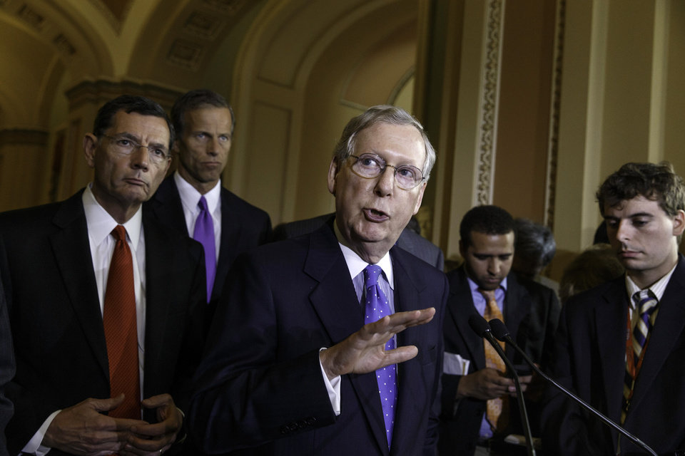 Photo - Senate Minority Leader Mitch McConnell of Ky., joined by, from left, Sen. John Barrasso, R-Wyo., and Sen. John Thune, R-S.D., speaks with reporters on Capitol Hill in Washington, Tuesday, June 17, 2014, after a Republican strategy session. President Barack Obama will meet with Congressional leaders at the White House on Wednesday to discuss the turmoil in Iraq. (AP Photo/J. Scott Applewhite)