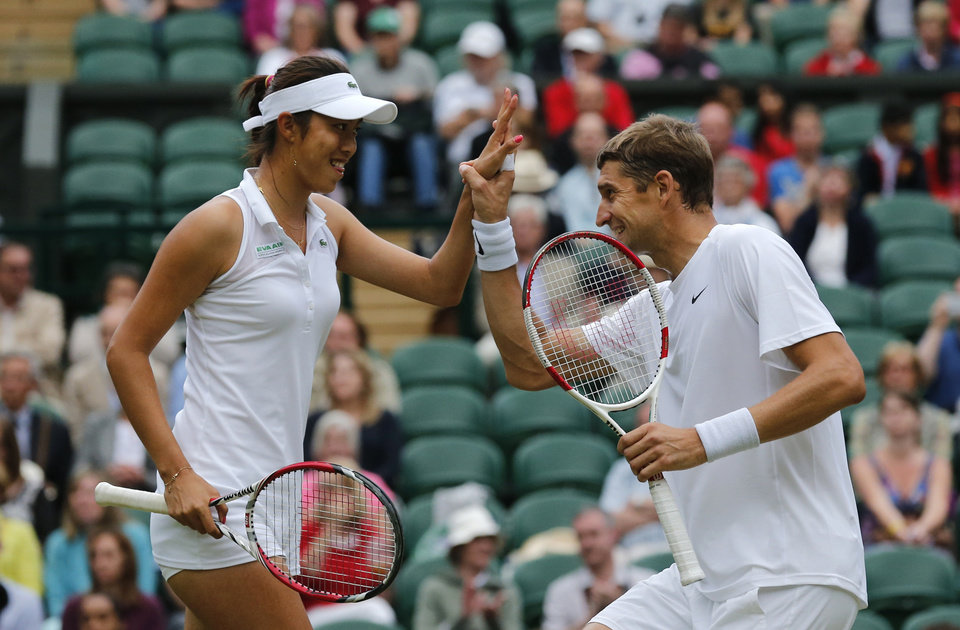 Photo - Max Mirnyi of Belarus, right, and Hao-Ching Chan of Taiwan celebrate a point during the mixed doubles final against Nenad Zimonjic of Serbia and Samantha Stosur of Australia at the All England Lawn Tennis Championships in Wimbledon, London, Sunday July 6, 2014. (AP Photo/Ben Curtis)