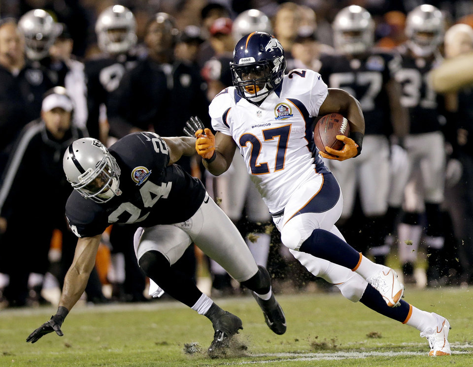 Photo - Denver Broncos running back Knowshon Moreno (27) carries the ball past Oakland Raiders cornerback Michael Huff (24) during the first quarter of an NFL football game in Oakland, Calif., Thursday, Dec. 6, 2012. (AP Photo/Marcio Jose Sanchez)