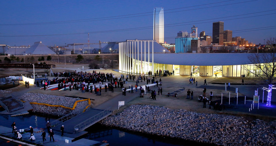 Photo - A crowd gathers in front of the Chesapeake Boathouse at dawn for the start of a sunrise memorial service for Aubrey McClendon in the Boathouse District on the Oklahoma River in 2016. The OKC Boathouse Foundation held a ceremonial paddle out in memory of McClendon, who died in a vehicle accident. [Jim Beckel/The Oklahoman]