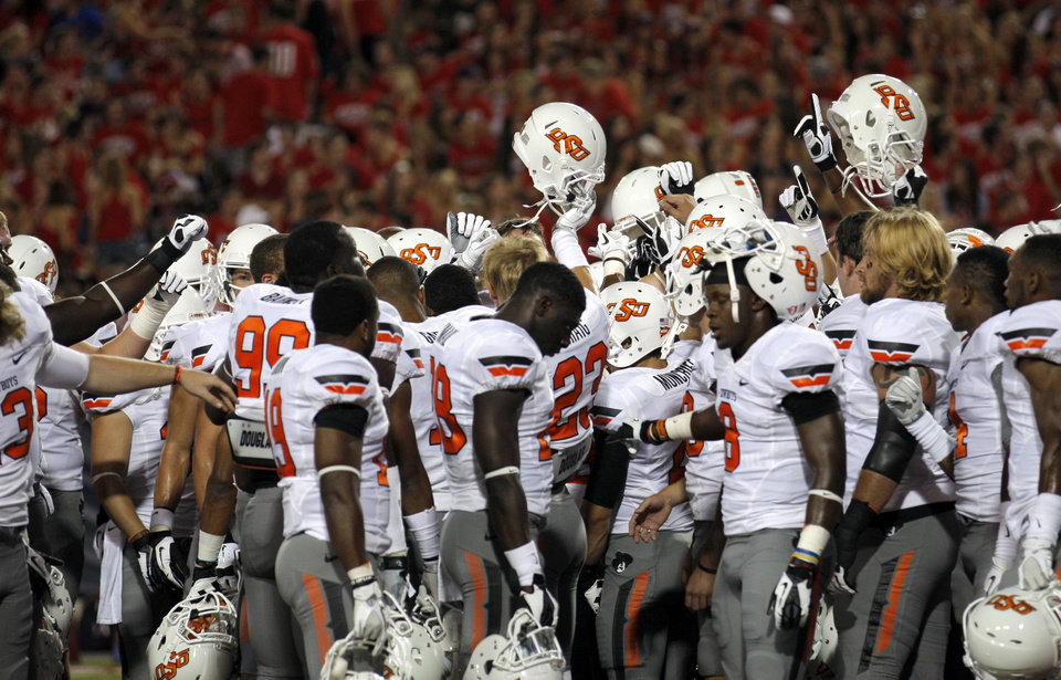 Photo - Oklahoma State huddles before the college football game between the University  of Arizona and Oklahoma State University at Arizona Stadium in Tucson, Ariz.,  Saturday, Sept. 8, 2012. Photo by Sarah Phipps, The Oklahoman