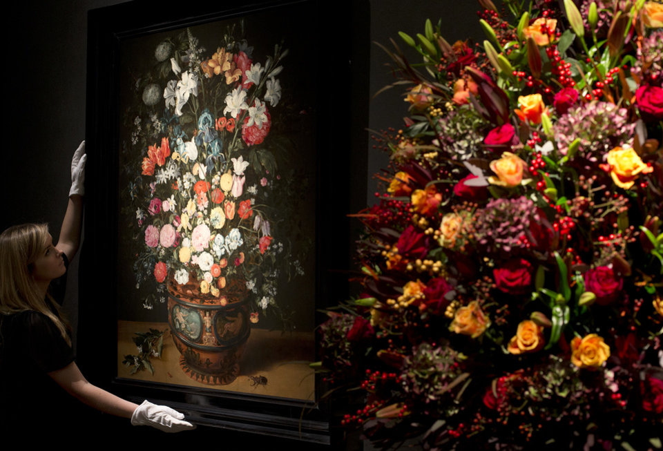 A Christie\'s employee adjusts a painting by Jan Breughel entitled \'Lilies, irises, roses and other flowers\' during a press preview at the auction house in London, Friday, Nov. 30, 2012. The painting has an estimated sale price of 1-1.5 million pounds (US$ 1.6-2.4 million, euro 1.25-1.85 million) when sold at auction on Dec.4 . (AP Photo/Alastair Grant)