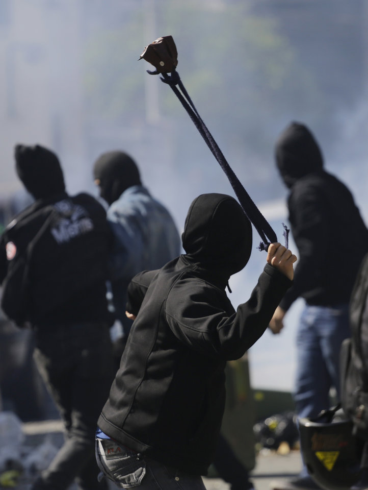 Photo - A protester winds up to sling a stone at police after clashes erupted in Sao Paulo, Brazil, Thursday, June 12, 2014. Police clashed with anti-World-Cup protesters who were trying to block a road part of the main highway leading to the stadium that hosts the opening match to the tournament.  in Sao Paulo, Brazil, Thursday, June 12, 2014. (AP Photo/Nelson Antoine)