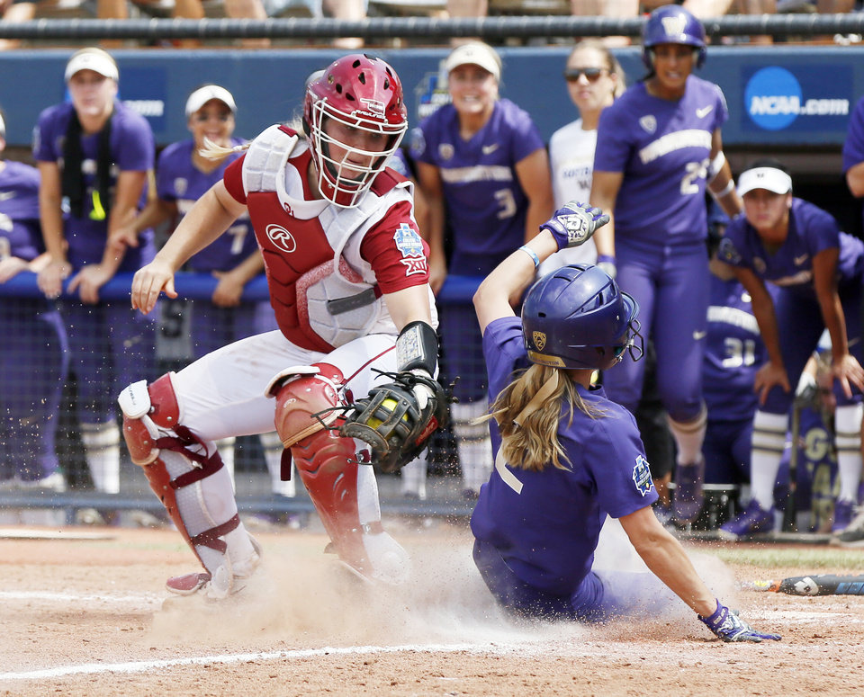 Photo - Washington's Trysten Melhart (2) slides home to score past Oklahoma's Lea Wodach (15) in the top of the fifth inning during the second game of the Women's College World Series between the Oklahoma Sooners (OU) and Washington Huskies at USA Softball Hall of Fame Stadium in Oklahoma City, Thursday, May 31, 2018. Washington won 2-0. Photo by Nate Billings, The Oklahoman