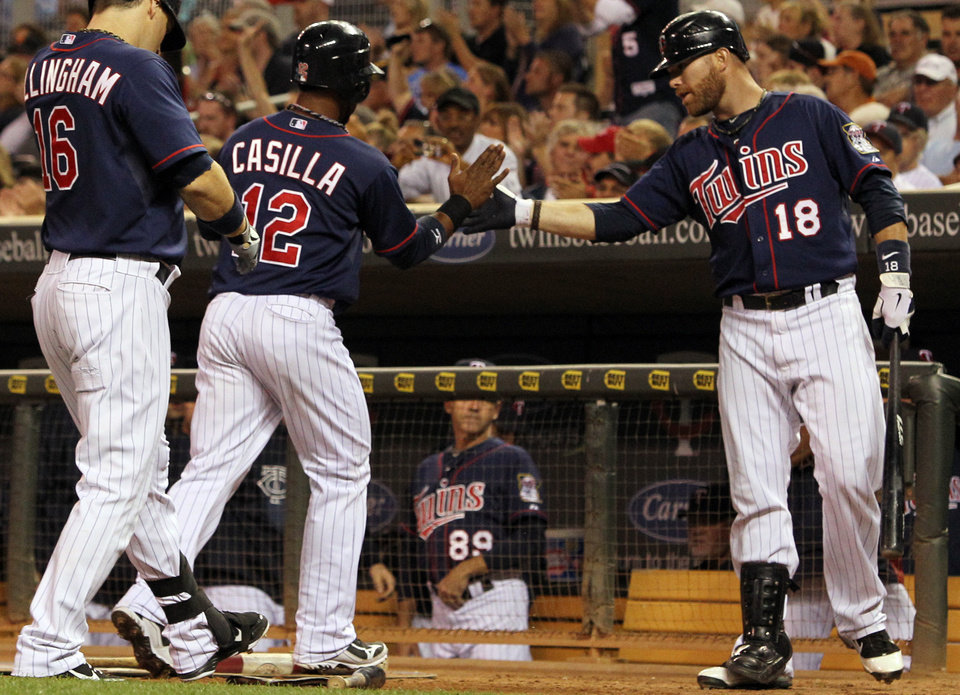 Photo -   Minnesota Twins' Alexi Casilla (12) is congratulated by teammate Ryan Doumit (18) after scoring on teammate Justin Morneau's sacrifice fly against Cleveland Indians starting pitcher Justin Masterson (63) during the fourth inning of a baseball game, Monday, Sept. 10, 2012, in Minneapolis. At left is Twins' Josh Willingham. (AP Photo/Genevieve Ross)