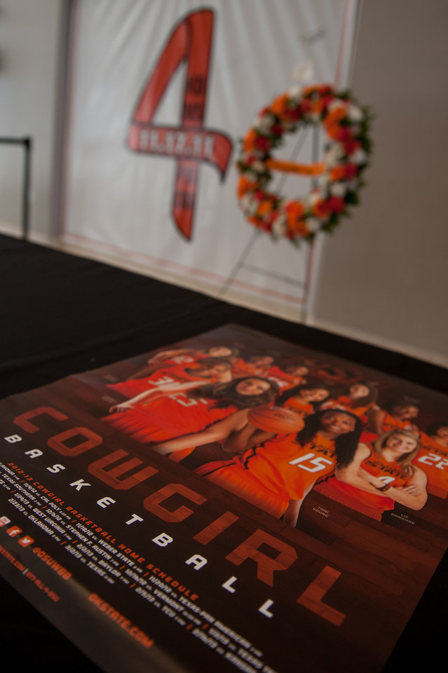 A table displays the 2012-2013 Cowgirl Basketball schedule poster in front of the Remember the 4 banner on Nov. 16, 2013 in Gallagher- Iba Arena in Stillwater, Okla. Oklahoma State University remembers the four members of the OSU women\'s basketball program on the one year anniversary of their accident. Photos by Mitchell Alcala for The Okahoman