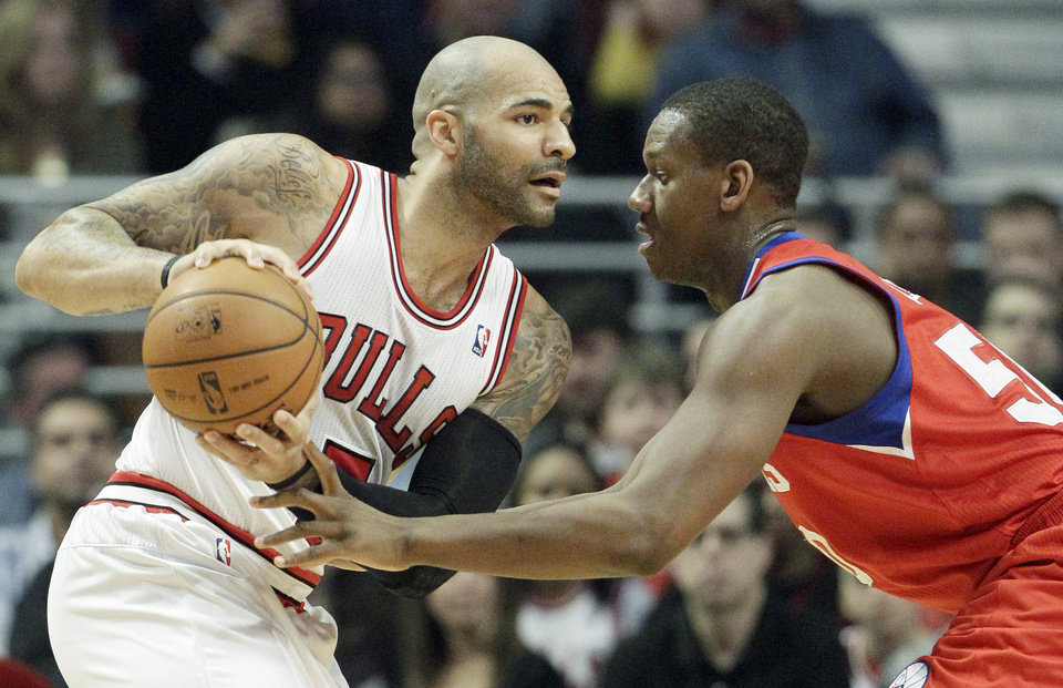 Chicago Bulls forward Carlos Boozer, left, looks to a pass as Philadelphia 76ers center Lavoy Allen guards during the first half of an NBA basketball game in Chicago on Saturday, Dec. 1, 2012. (AP Photo/Nam Y. Huh)