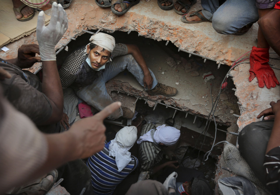 Photo - A Bangladeshi rescuer looks out from a hole cut in the concrete as he looks for survivors at the site of a building that collapsed Wednesday in Savar, near Dhaka, Bangladesh, Thursday, April 25, 2013. By Thursday, the death toll reached at least 194 people as rescuers continued to search for injured and missing, after a huge section of an eight-story building that housed several garment factories splintered into a pile of concrete.(AP Photo/Kevin Frayer)