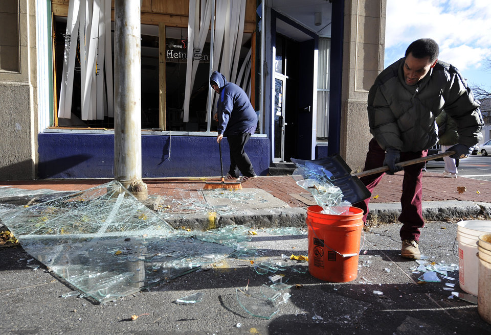 Photo -   Robert Spano, left, and Alan Hugley clean up broken glass, Saturday, Nov. 24, 2012, outside of Punta cana Restaurant & Bar, a few blocks from the site of a Friday-evening gas explosion that leveled a strip club in Springfield, Mass. (AP Photo/Jessica Hill)