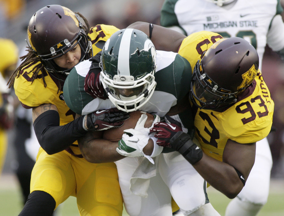 Photo -   Michigan State running back Le'Veon Bell (24) is tackled by Minnesota defensive back Derrick Wells (13) and defensive end Ben Perry (93) after a 40-yard run during the first half of an NCAA college football game, Saturday, Nov. 24, 2012, in Minneapolis. (AP Photo/Paul Battaglia)