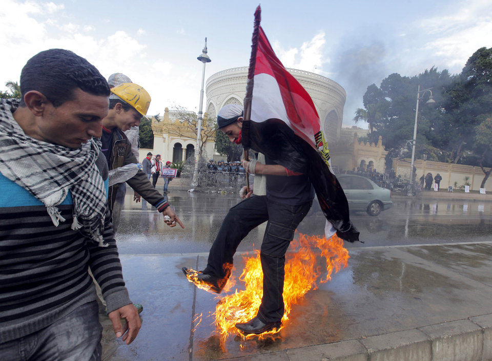 Photo - An Egyptian protester tries to escape from fire after he burned an anti-Mohammed Morsi banner in front of the presidential palace in Cairo, Egypt, Friday, Feb. 1, 2013. Thousands of Egyptians marched across the country, chanting against the rule of the Islamist President Mohammed Morsi, in a fresh wave of protests Friday, even as cracks appeared in the ranks of the opposition after its political leaders met for the first time with the rival Muslim Brotherhood. (AP Photo/Amr Nabil)