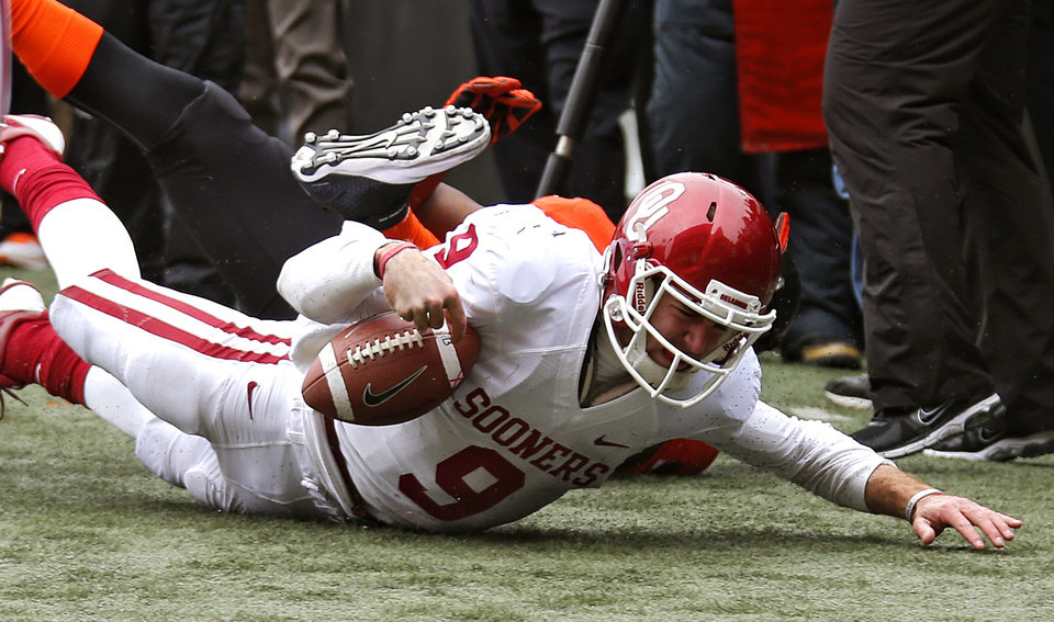 Oklahoma's Trevor Knight (9) hits the turf after being forced out of bound during the Bedlam college football game between the Oklahoma State University Cowboys (OSU) and the University of Oklahoma Sooners (OU) at Boone Pickens Stadium in Stillwater, Okla., Saturday, Dec. 7, 2013. Knight was injured on the play, and never returned to the game. Photo by Chris Landsberger, The Oklahoman