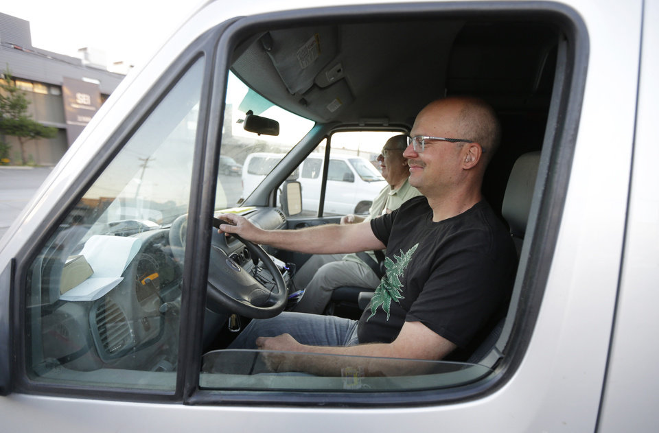 Photo - Phil Tobias, director of Sea of Green Farms, front, drives a delivery van in Seattle with farm owner Bob Leeds, as they set out on their first delivery of recreational marijuana to a store in Bellingham, Wash., on Tuesday, July 8, 2014. It was the first delivery for the company since retail licenses were issued by the state on Monday. (AP Photo/Ted S. Warren)