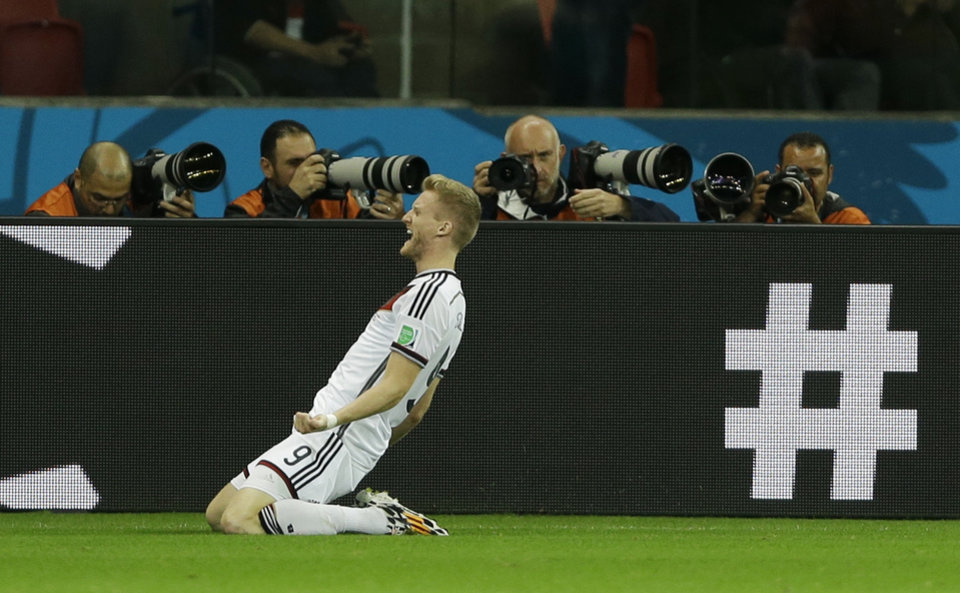 Photo - Germany's Andre Schuerrle celebrates after scoring his side's first goal in overtime during the World Cup round of 16 soccer match between Germany and Algeria at the Estadio Beira-Rio in Porto Alegre, Brazil, Monday, June 30, 2014. (AP Photo/Kirsty Wigglesworth)