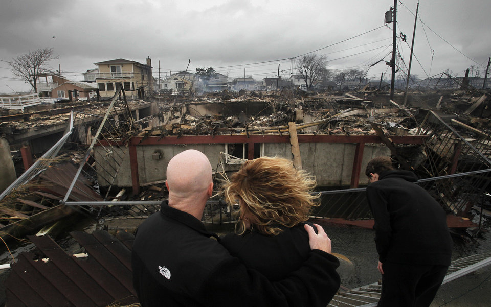 Robert Connolly, left, embraces his wife Laura as they survey the remains of the home owned by her parents that burned to the ground in the Breezy Point section of New York, Tuesday, Oct. 30, 2012. More than 50 homes were destroyed in the fire which swept through the oceanfront  community during superstorm Sandy. At right is their son, Kyle. (AP Photo/Mark Lennihan) ORG XMIT: NYML109
